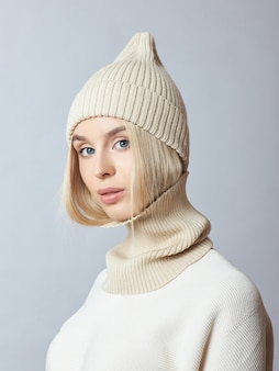 Donna in abiti primaverili, sciarpa snood, cappello e guanti. la ragazza è bionda con gli occhi azzurri.