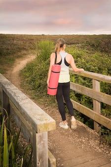 Donna in abiti sportivi con una stuoia rosa cammina dopo l'allenamento nel parco al tramonto