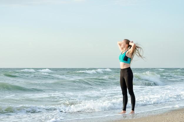Donna in abiti sportivi sulla spiaggia regola i suoi capelli. luce del mattino