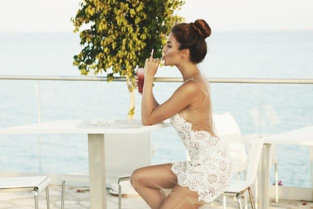 Donna in abito bello con un bicchiere di cocktail
