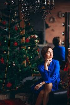 Donna in abito bello seduto vicino all'albero di natale