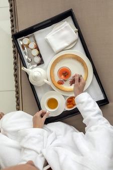 Donna in abito bianco bere tè