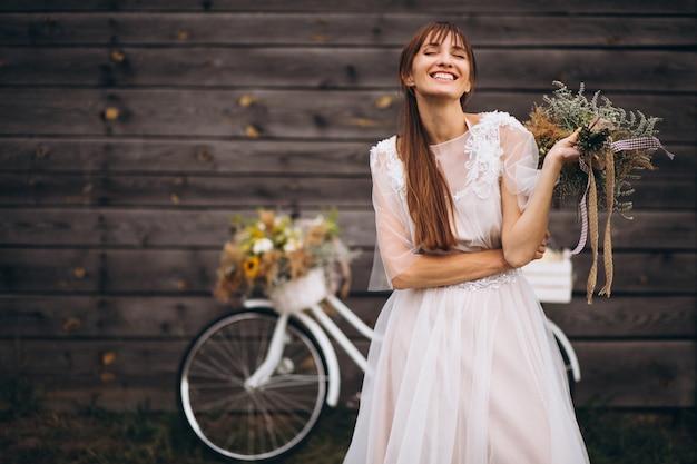 Donna in abito bianco con bicicletta dalla parete in legno