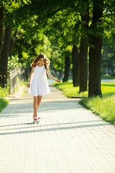 Donna in abito bianco con uno skateboard rosa