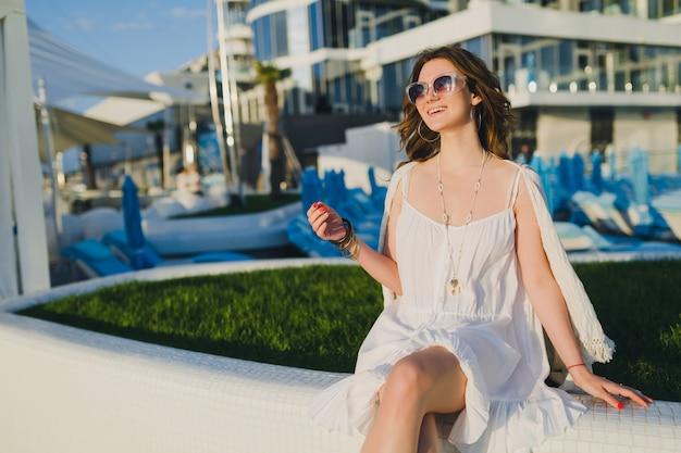 Donna in abito bianco in hotel resort estivo, indossando occhiali da sole e accessori alla moda