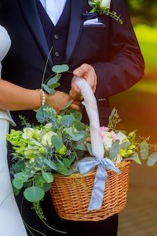 Donna in abito bianco in possesso di un cesto di fiori senza volto