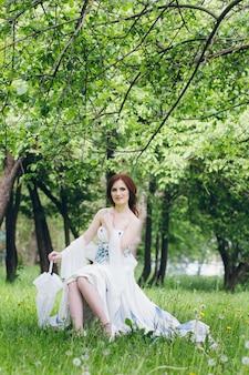 Donna in abito bianco lungo nel giardino estivo