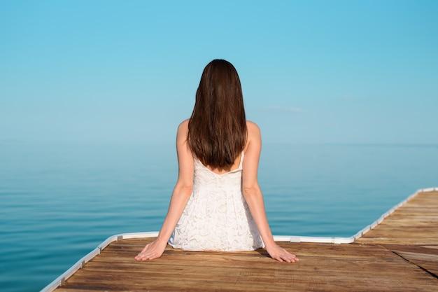 Donna in abito bianco seduto sul molo e guardando in lontananza