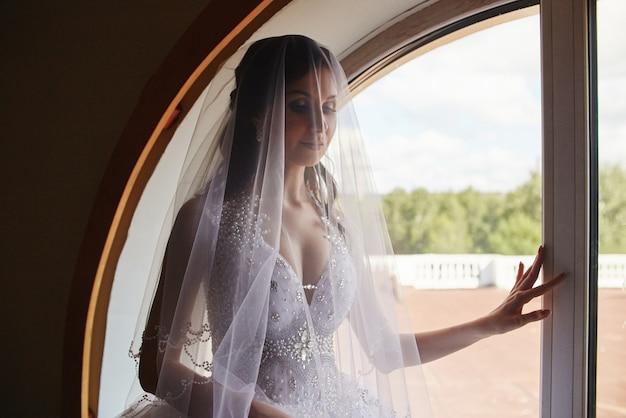 Donna in abito da sposa in piedi alla finestra. cerimonia di nozze aspettante della sposa