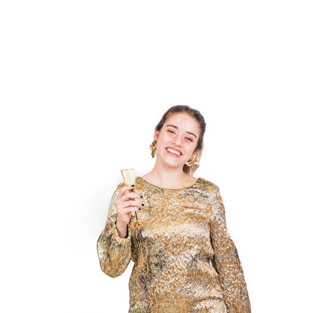 Donna in abito dorato in piedi con un bicchiere di champagne