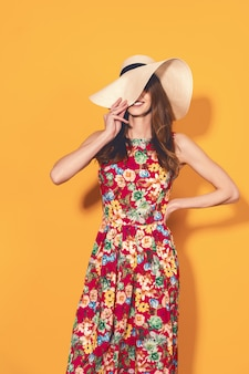 Donna in abito floreale e cappello