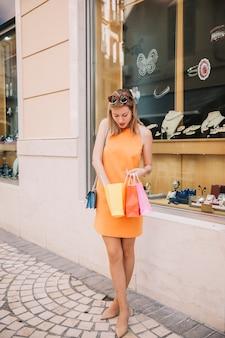 Donna in abito giallo con borse di fronte al negozio di gioielli con borse