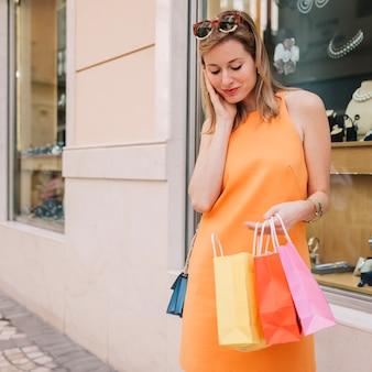 Donna in abito giallo con tre borse per la spesa