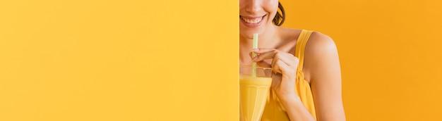Donna in abito giallo con un bicchiere di succo