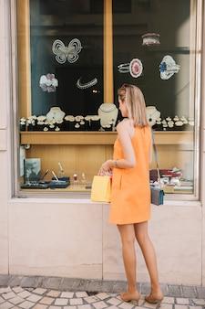 Donna in abito giallo di fronte al negozio di gioielli