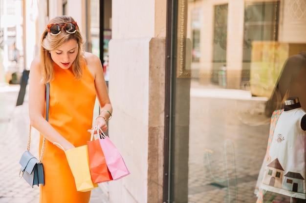 Donna in abito giallo guardando in borse