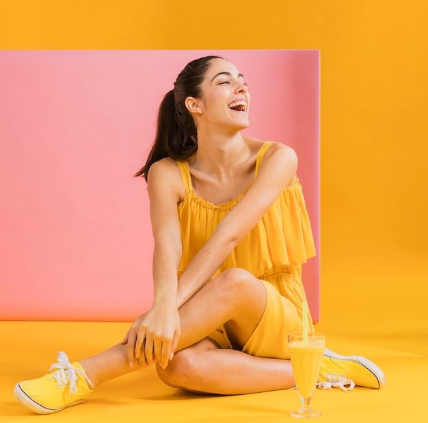 Donna in abito giallo, seduta sul pavimento