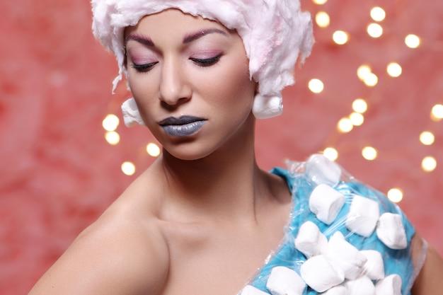 Donna in abito insolito fatto di marshmallow e parrucca di zucchero filato