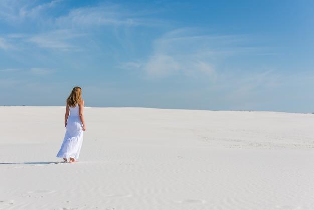 Donna in abito lungo bianco a piedi nel deserto