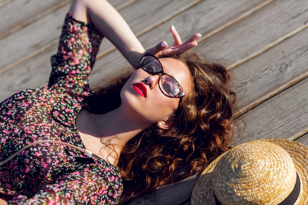 Donna in abito lungo colorato e cappello di paglia posa sdraiato sul pavimento di legno
