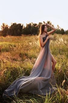 Donna in abito lungo grigio in natura al tramonto
