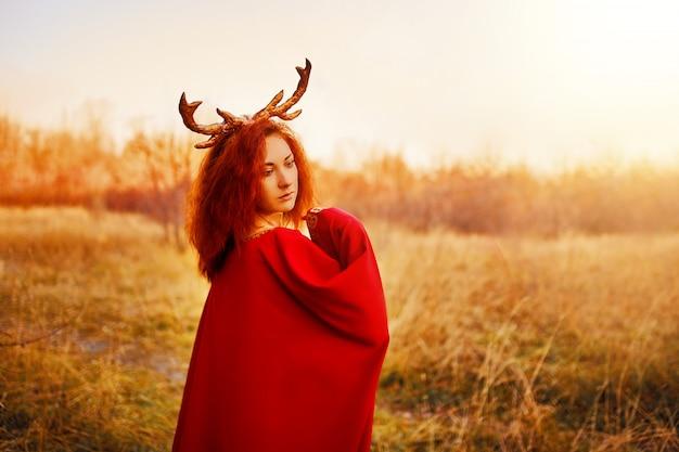 Donna in abito lungo rosso con corna di cervo nella foresta d'autunno.