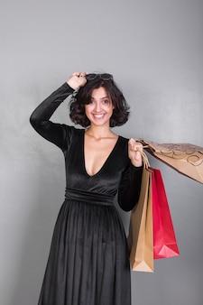 Donna in abito nero con borse della spesa