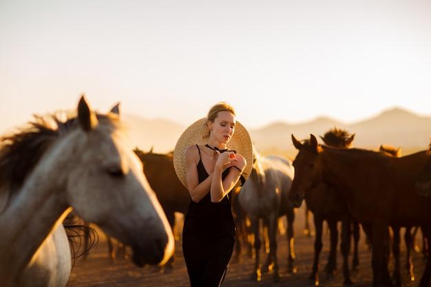 Donna in abito nero tra cavalli selvaggi