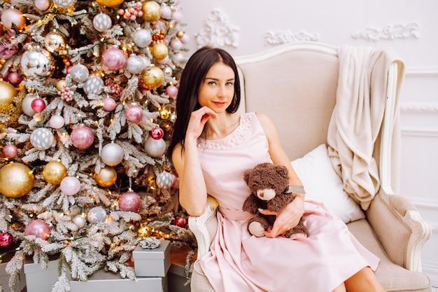 Donna in abito rosa con piccolo orso seduto su una sedia vicino all'albero di natale leggero.