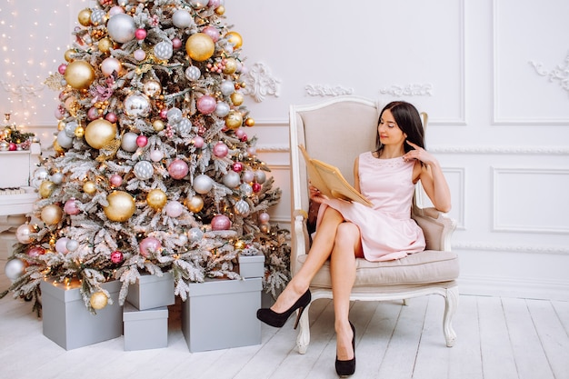 Donna in abito rosa seduto su una sedia vicino all'albero di natale leggero.