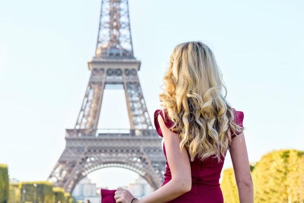 Donna in abito rosso alla torre eiffel in francia