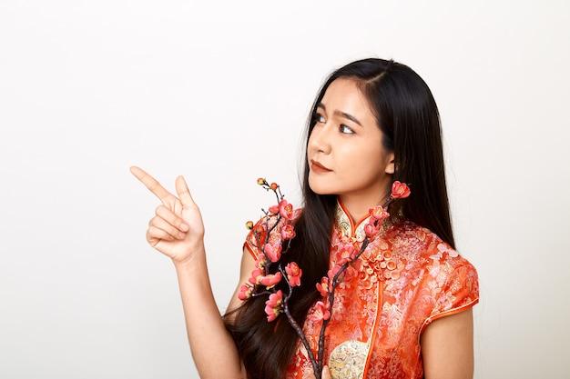 Donna in abito rosso cinese tradizionale con fiori di prugna