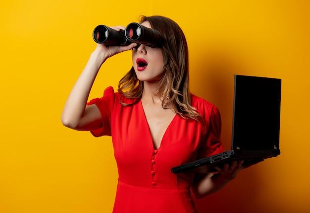 Donna in abito rosso con binocolo e computer portatile