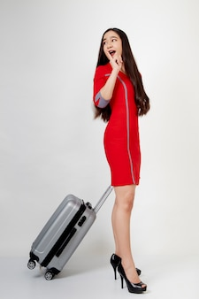 Donna in abito rosso con la valigia