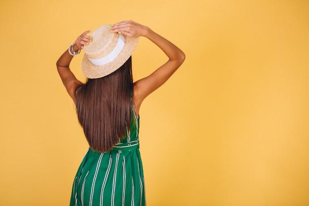 Donna in abito verde e cappello su sfondo giallo