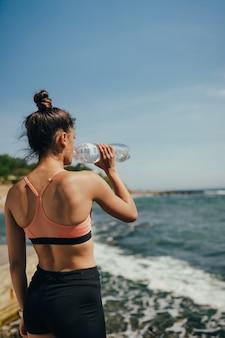 Donna in abito yoga bere acqua fresca dalla bottiglia dopo l'esercizio sulla spiaggia