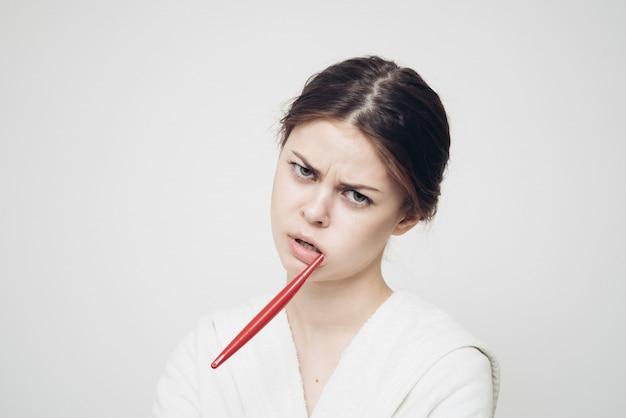 Donna in accappatoio a lavarsi i denti