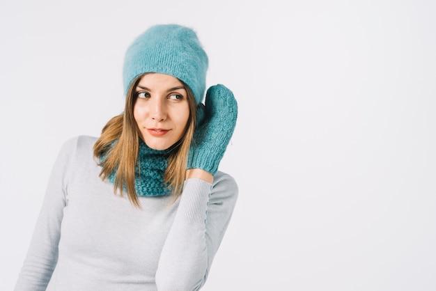Donna in accessori caldi tenendo la mano vicino all'orecchio