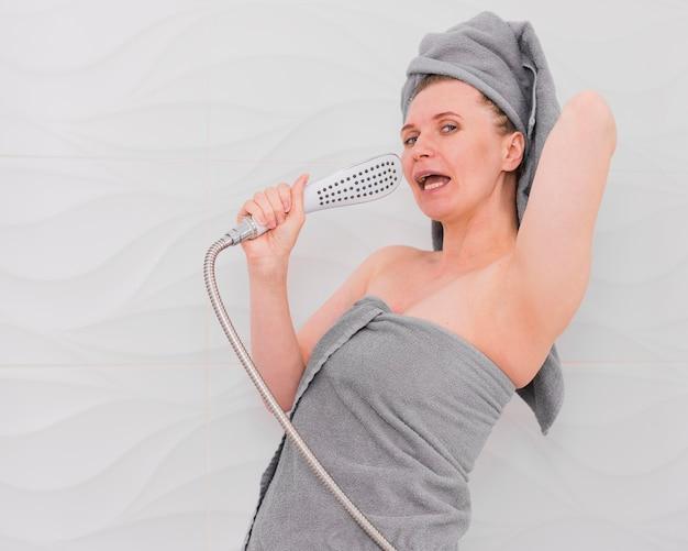 Donna in asciugamani che canta nel colpo medio del bagno