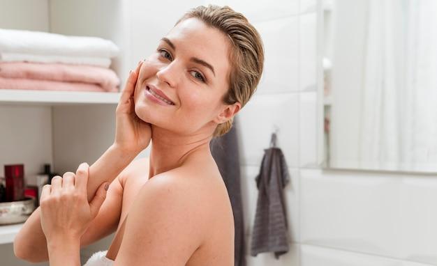 Donna in asciugamano che riposa la testa nella mano