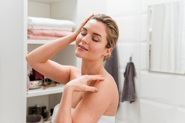 Donna in asciugamano con gli occhi chiusi