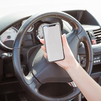 Donna in auto guardando il modello di smartphone