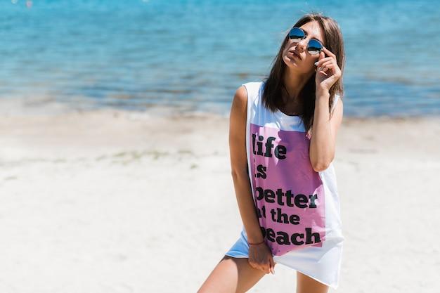 Donna in autoreggente baggy che regola gli occhiali da sole