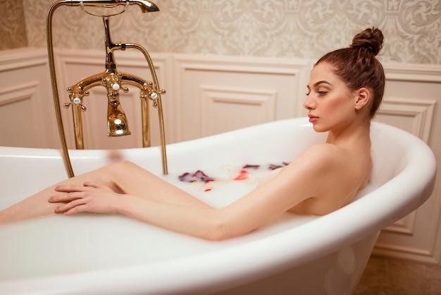 Donna in bagno con petali di rosa e schiuma