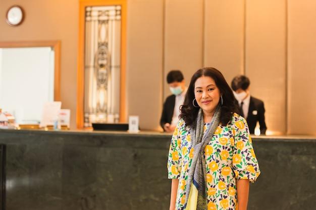 Donna in bel vestito in piedi davanti alla reception dell'hotel.