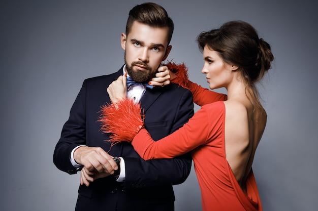 Donna in bellissimo vestito rosso e uomo che indossa abito classico blu con farfallino.