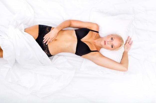 Donna in biancheria intima che si trova nel suo letto