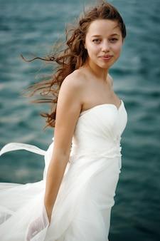 Donna in bianco vicino al mare in tempesta