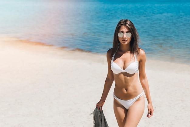 Donna in bikini a piedi dal mare