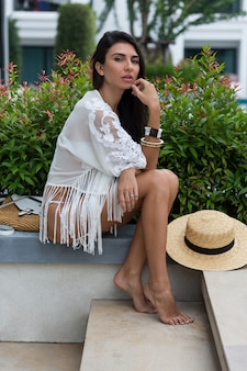Donna in bikini bianco in posa in hotel moderno in thailandia indossando abiti da spiaggia boho alla moda